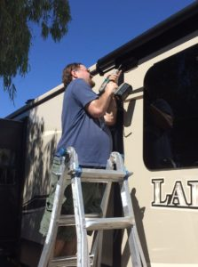 A man with light skin standing on a ladder, holding a drill and working on an RV near its roof.